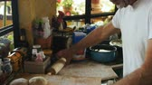 flatten : Tilt up and down of a man preparing bread or dough with a rolling pin for pizza on a wooden cutting board in his home kitchen Stock Footage