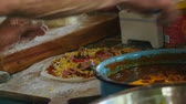 processado : A man spreads meat toppings on a pizza with his hands in a gourmet kitchen