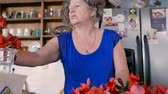wazon : A woman in her 60s arranges fresh cut red flowers in a vase in her modern kitchen - dolly shot Wideo