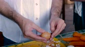 peel an egg : A middle aged man peels a hard boiled egg while working beside an elder man in a home kitchen - pan up