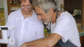 молоть : A middle aged man and older senior have fun working together grinding fish in a modern kitchen