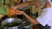 matzo : An elderly man adds paprika from a plastic bag to a pot of chicken soup in his kitchen without measuring the amount