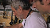 торжества : An elder man and middle aged man work together over a hot stove as they are preparing a meal together