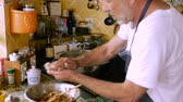 matzo : A man in his 60s makes homemade maztah balls with his hands and places them in a pot
