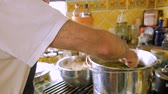 matzo : An older Jewish man stirs a large pot of soup with herbs in it on a gas stove in slow motion