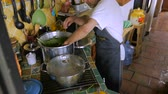 matzo : A man in his 60s puts cut cabbage into a large pot of soup with herbs - high angle