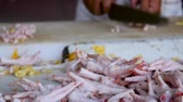 cut off : Close up of whole chicken feet while a man removes the claws with a large knife in the background - dolly shot