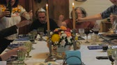 champanhe : A group of friends and family pour champagne at dinner party or passover seder celebration.