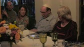 yarmulke : A man reads from a book (Haggadah) at a dinner table during a passover seder Stock Footage
