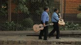 san miguel : SAN MIGUEL DE ALLENDE, MEXICO - CIRCA MAY 2016 - Two guitarist musicians walk down the street in slow motion