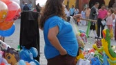 san miguel : SAN MIGUEL DE ALLENDE, MEXICO - CIRCA MAY 2016 - An overweight balloon and toy vendor in a public space hands out change in slow motion