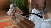 optometria : Close up of man repairing prescription glasses with tiny screwdriver - handheld