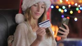 cartão : A happy attractive young female shopper wearing a Santa hat finishes her online purchase on her smart phone during the holidays with Christmas lights in the background - push in
