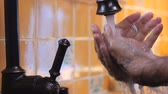 thoroughly : A man washes his hands under a faucet and rinses off the soap in slow mo - close up