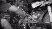 зажимное приспособление : Black and white dolly shot of a mechanic cleaning and draining gasoline from a partially disassembled motorcycle in Bali, Indonesia utilizing simple tools in a basic workshop Стоковые видеозаписи