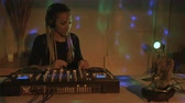транс : Hand held of an African American woman DJ mixing music in an underground club