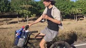 saúde : A man in his early 30s cheers the camera while riding a beach cruiser bike on an empty paved road while drinking wine. Stock Footage