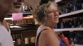 frasco pequeno : A baby boomer woman and man shopping for glasses in a factory in slow motion in the summer