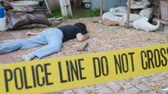 bizonyíték : Caucasian white male dead murdered body lying on ground at crime scene with Police Line Do Not Cross tape outside with hammer Stock mozgókép