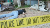 bizonyíték : Caucasian white man dead murdered body lying on ground at crime scene with Police Line Do Not Cross tape outside with hammer rack focus Stock mozgókép