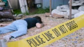bizonyíték : Caucasian white male dead murdered body lying on ground at crime scene with Police Line Do Not Cross tape outside with hammer rack focus