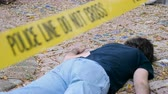 bizonyíték : A dead murdered killed man roped off with Police Line Do Not Cross tape at crime scene - dolly shot
