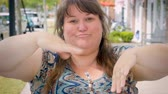işlenmiş : A disappointed full figured woman gives two thumbs down outside on a city sidewalk Stok Video