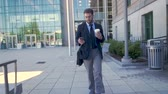 честолюбие : Ambitious executive millennial businessman with beard, briefcase, and to go coffee cup walking away from modern glass building and browsing on smartphone technology app in slow motion stabilized shot Стоковые видеозаписи