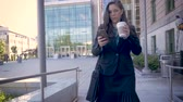 cihaz : A successful millennial businesswoman executive walking away from a modern office building using smartphone technology app drinking togo coffee slow motion stabilized shot Stok Video