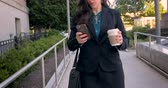 cihaz : Attractive professional millennial businesswoman or lawyer on mobile phone technology walking on walkway with briefcase and to go coffee cup in 4k stabilized shot