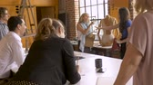 работодатель : Two women presenting their idea to their coworkers at a creative business meeting where employees are sharing ideas in slow motion hand held stabilized shot