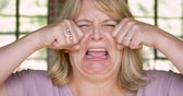 somber : Unhappy woman crying and wiping her face with her hands - waa waah