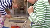 торжества : Older brother helping his younger little sister coloring and painting easter eggs together in slow motion outside for the holiday celebration