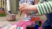 торжества : Two young children painting and dyeing easter eggs together outside in slow motion