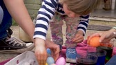 торжества : Cute little 3 year old girl grabbing painted colored easter eggs from a crate with her family together for the traditional holiday celebration