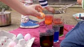 торжества : Young boy and girl siblings help their mother coloring easter eggs for the traditional holiday celebration