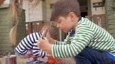 торжества : A millennial mother and her two young kids painting and easter eggs together outside in slow motion