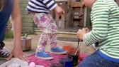 торжества : Mother and her two young children dyeing easter eggs together outside in slow motion