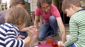 торжества : Family of four working on a fun arts and crafts project together in slow motion