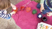 торжества : Overhead of young boy and girl coloring easter eggs and putting them in an egg crate