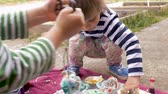 торжества : Adorable young boy and girl making colorful arts and crafts project outside in slow motion