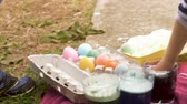 торжества : Cute young 3 year old girl grabbing a colored easter egg with her hand outside in slow motion
