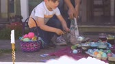 торжества : Millennial mother and young son coloring and dyeing easter eggs together outside in slow motion Стоковые видеозаписи