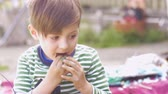 торжества : Adorable happy little boy eating chocolate and nodding his head outside in slow motion