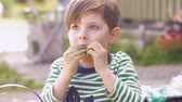 торжества : Cute little boy giving thumbs up while enjoying eating chocolate in slow motion outside