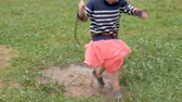 lamacento : Cute little 2 year old girl in pink skirt running through puddle and looking at camera outside in slow motion during spring or summer