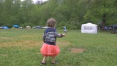 imaginação : Adorable 2 year old girl in a pink skirt playing and pretending to fish with a stick in a muddy puddle while camping at a festival in slow motion Stock Footage