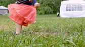 imaginação : Close up low angle of a young toddler girl jumping over a puddle in the grass at a festival in slow motion Stock Footage