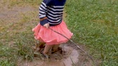 lamacento : Overhead of a young girl splashing around in a mud puddle in a skirt in slow motion outside Stock Footage