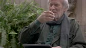 сакэ : Candid moment of a healthy attractive senior man in his 70s laughing and drinking sake with a tablet sitting outside